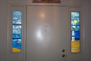 Lighthouse Door Panels - This pair of 9.5 38 front door panel features opaque glass for privacy , but also incorporates some visibility thru the sky blue glass. It is framed in a stained oak trim to match the existing trim of the home.