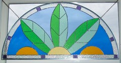 Summer - This piece was designed to fit a standard Anderson palladium window measuring 30x 15. It is designed around the mullions that come with the window.It features a rough rolled glass in 2 different greens and our signature amber glass.