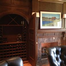 Quarter Sawn Oak library Cabinetry - Wine storage closet with round top doors, wainscot paneling, fireplace surround with hand carved Corbels